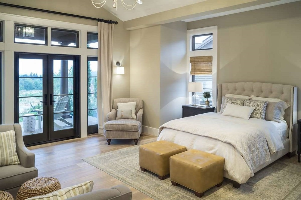 The bright and spacious bedroom has a bed with a cushioned headboard that matches the walls and the cushioned armchairs.