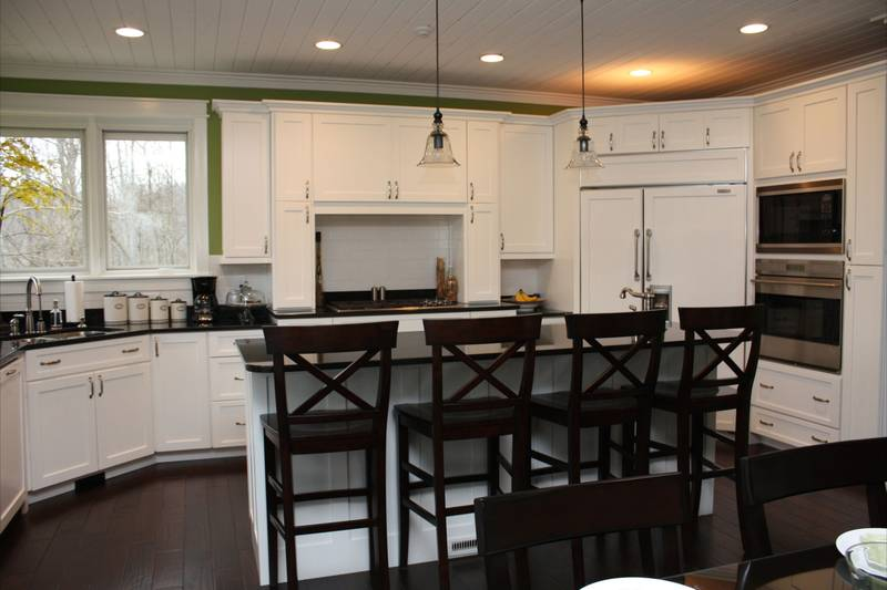The kitchen is equipped with stainless steel appliances, white cabinetry, and a breakfast bar lined with dark wood counter chairs and topped with pendant lights.