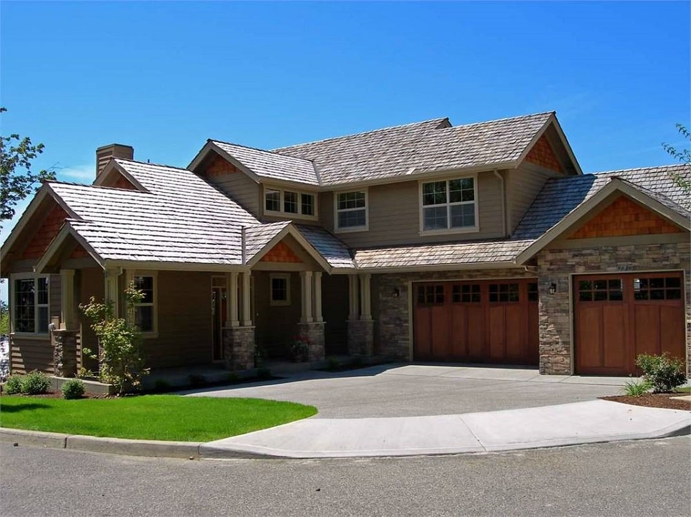 This is a front view of the house with a wide asphalt driveway leading to the garage doors and main entrance. These two sides are then complemented by miniature gardens of grass lawn and shrubs.