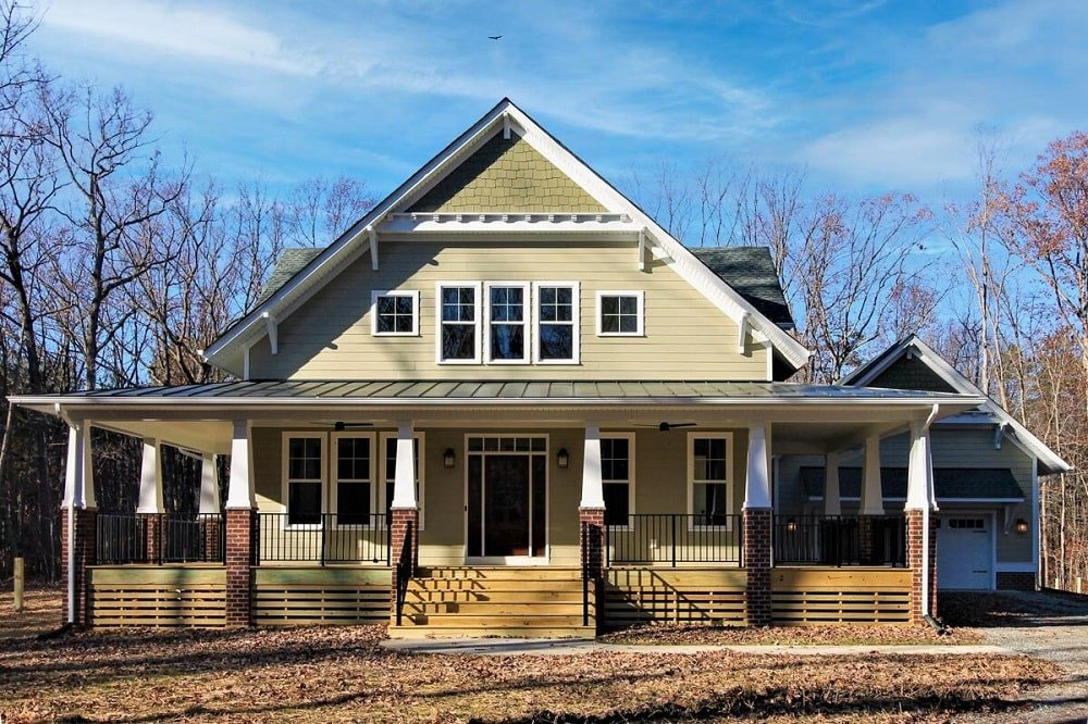 This is a front view of the farmhouse-style home with two levels and a wrap-around porch supported by multiple pillars.