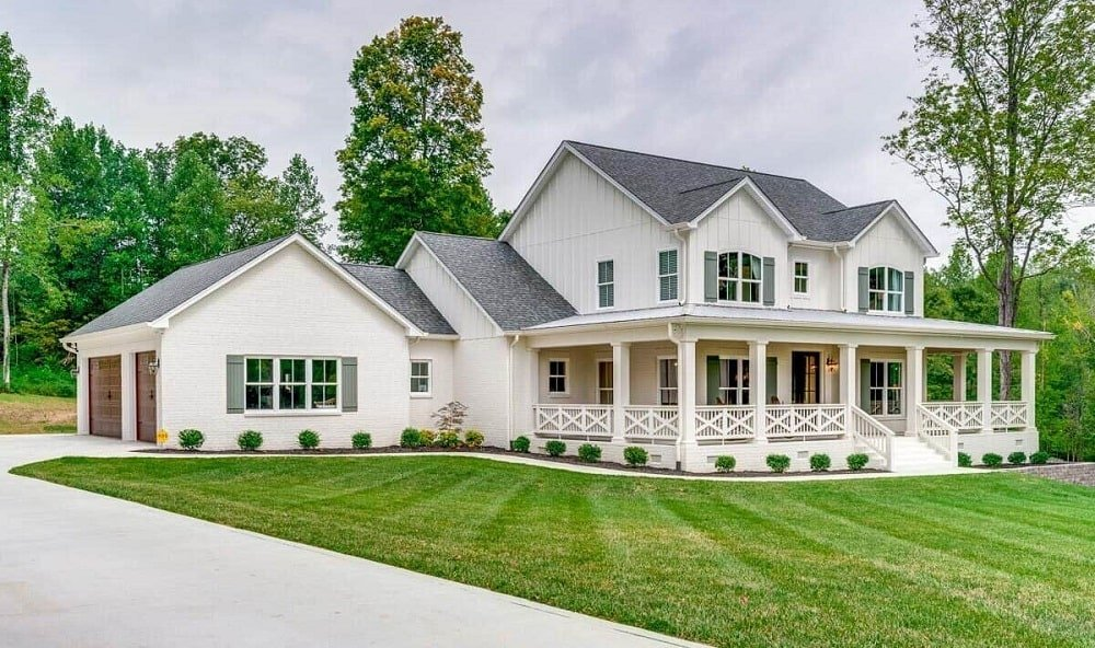 This is a farmhouse-style home with two stories, a garage on the side with a walkway outside leading to the main entrance that has a wrap-around porch lined by railings.