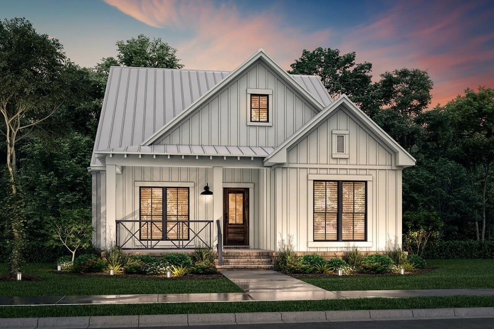 This farmhouse style home has a consistent light beige tone to its exterior walls with a striped pattern texture complemented by the warm yellow lights of the glass windows and door that glow from the interior lights.