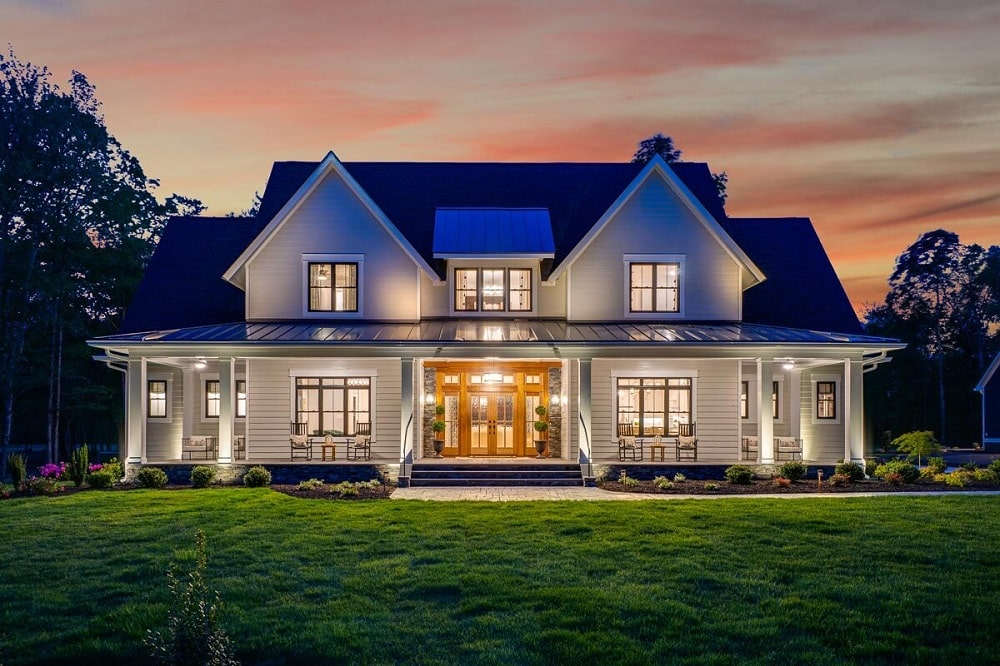 This is a nighttime view of this farmhouse-style home with warm indoor and outdoor lighting that goes well with the bright exterior walls and dark roof.
