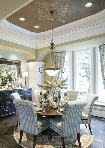 This is a Northwest-style dining room with a large circular wooden dining table surrounded by cushioned chairs and topped with a dome pendant light hanging from a tray ceiling.