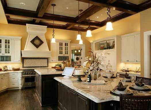 This kitchen has dark wooden exposed beams on its ceiling along with pendant lights that hang over the large T-shaped kitchen island with an attached table to it.