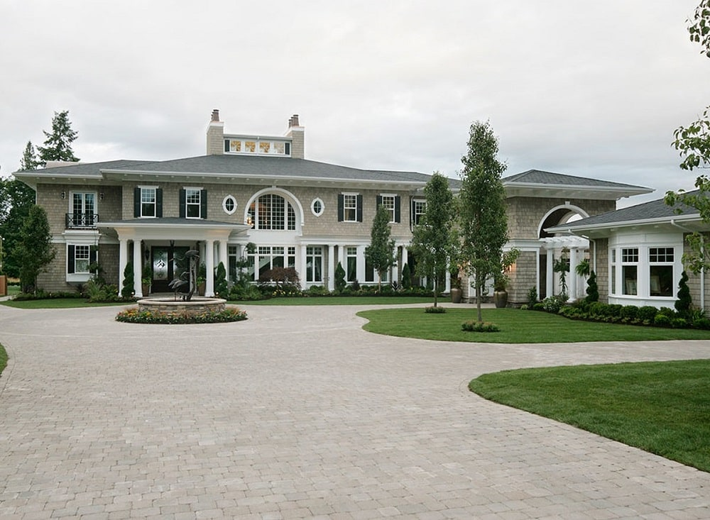 This is the front of the house that showcases the landscaping with wide driveways and walkways adorned by the grass lawns, shrubs and tall trees that bring colorto the exterior walls of the house.