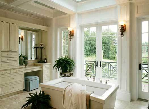 This is a primary bathroom with a freestanding bathtub in the middle across from the glass doors that are flanked with sconces. On the side is the vanity area with light beige cabinets and a large mirror.