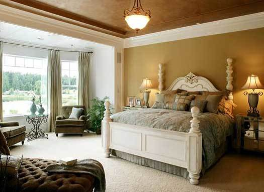 This primary bedroom has earthy tones on its tray ceiling and wall that complement the white four-poster bed topped with a small semi-flush dome lighting with warm light.