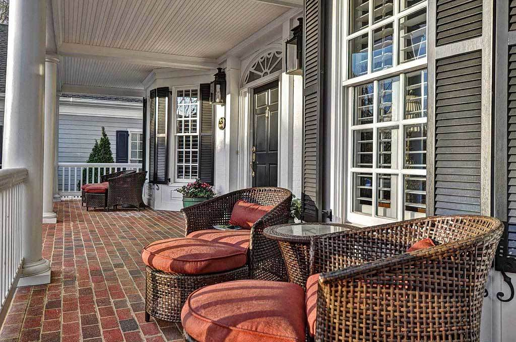 The covered porch is furnished with cushioned wicker chairs over brick flooring.