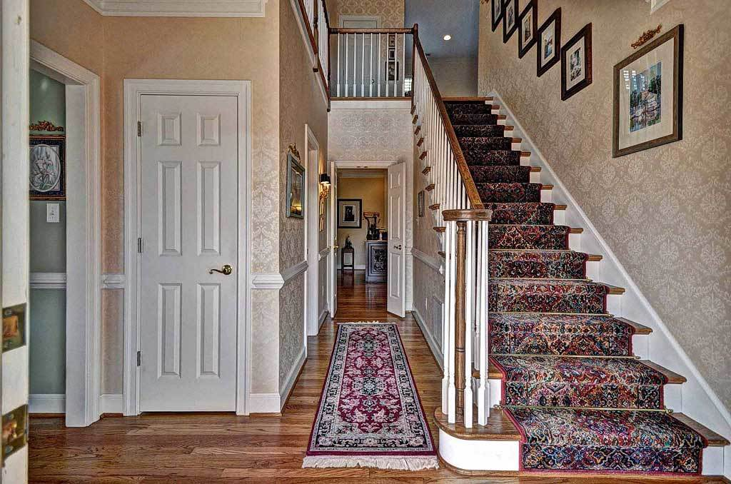 Foyer with a tasseled runner and a traditional staircase dressed in a vintage carpet.