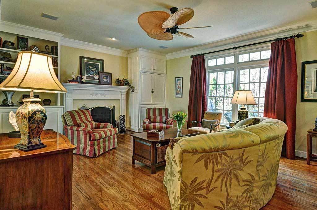 Family room with patterned seats, a fireplace, and a white french door that opens to the rear deck.
