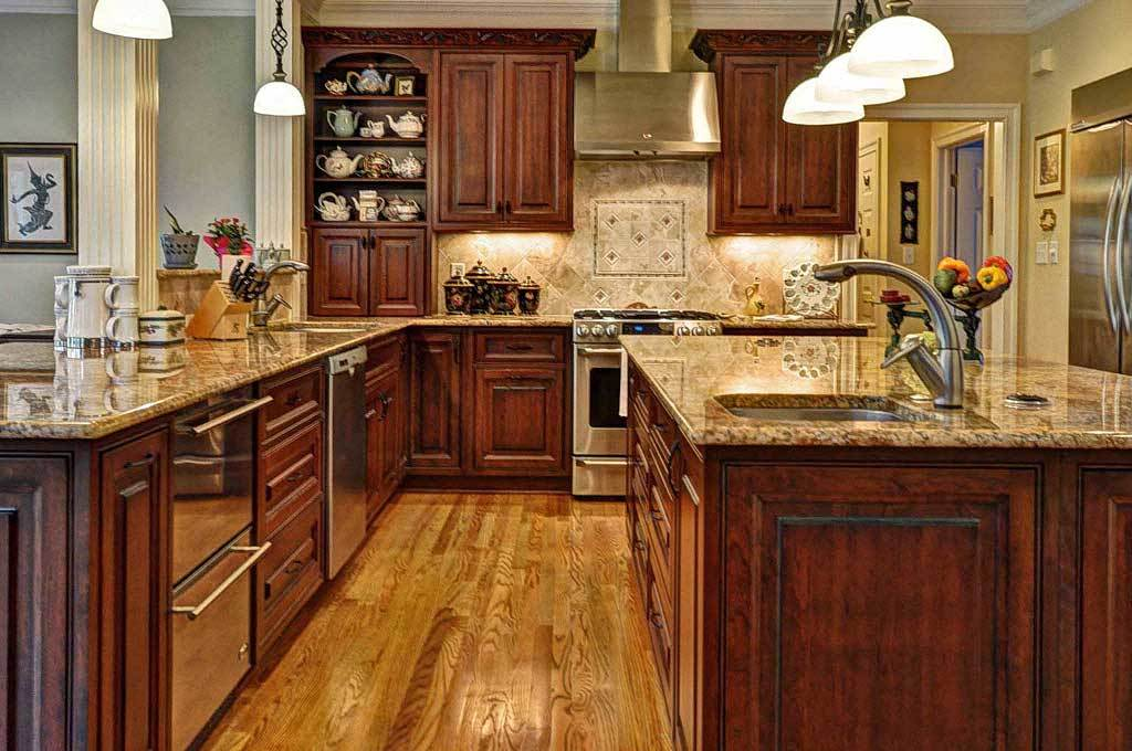 The kitchen offers granite countertops, natural wood cabinetry, and a large center island fitted with a sink.