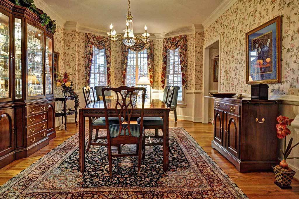 Formal dining room graced with floral wallpaper, lower wainscoted walls, and a classic area rug topped with a wooden dining set.