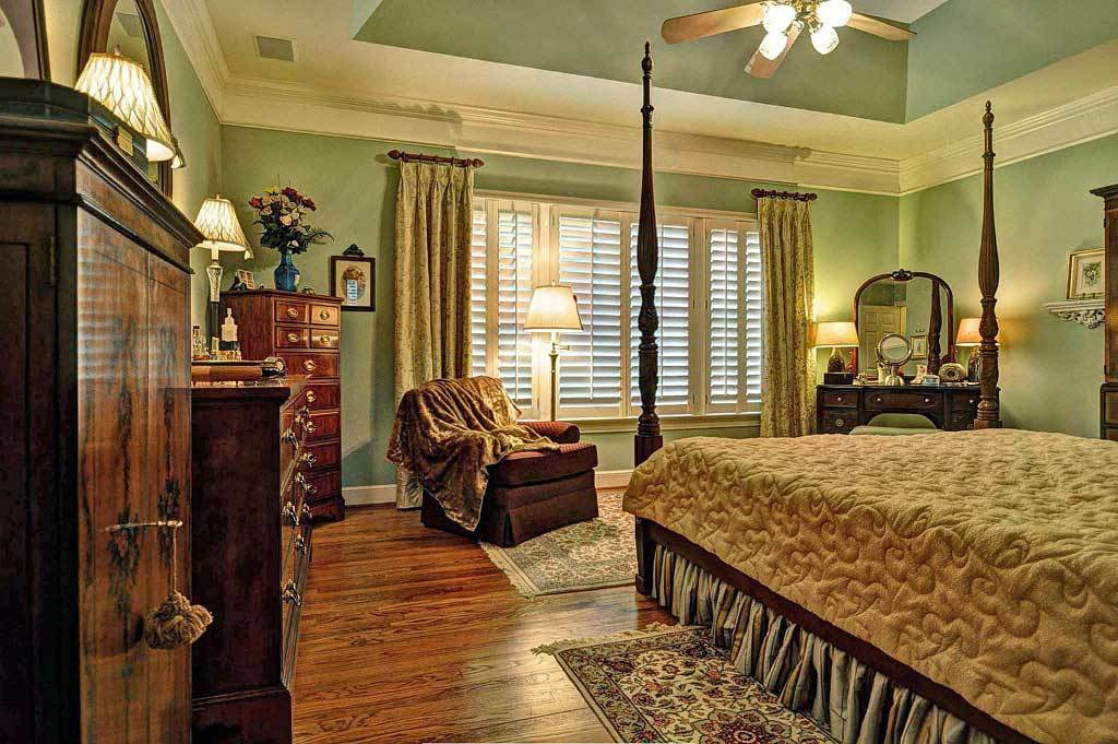 The primary bedroom has a coved ceiling and mint green walls warmed by traditional table and floor lamps.