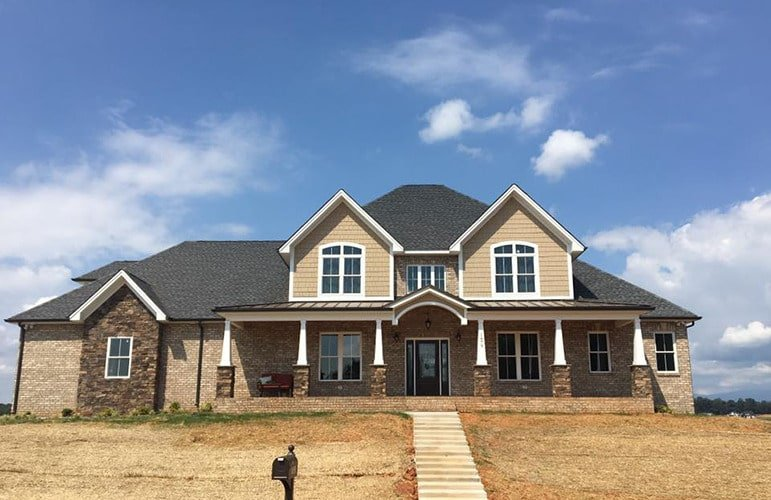 This is an exterior look at a two-story famhouse-style home with large dormer windows above the front poch that is supported by a row of pillars that go well with the exterior walls and roof.