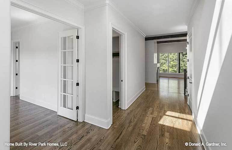 Entry hallway with natural hardwood flooring leading to the open living space.
