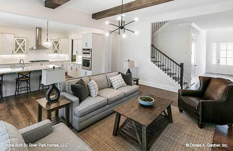 Living room with a gray sectional, wingback leather armchair, wooden tables, and a contemporary chandelier that hangs from the beamed ceiling.