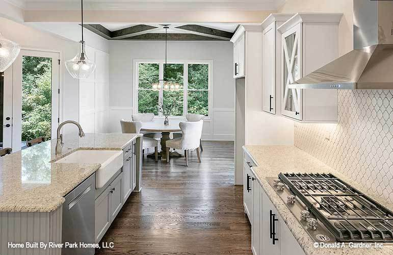 The kitchen sits across the dining area that's brightened by a trio of windows.