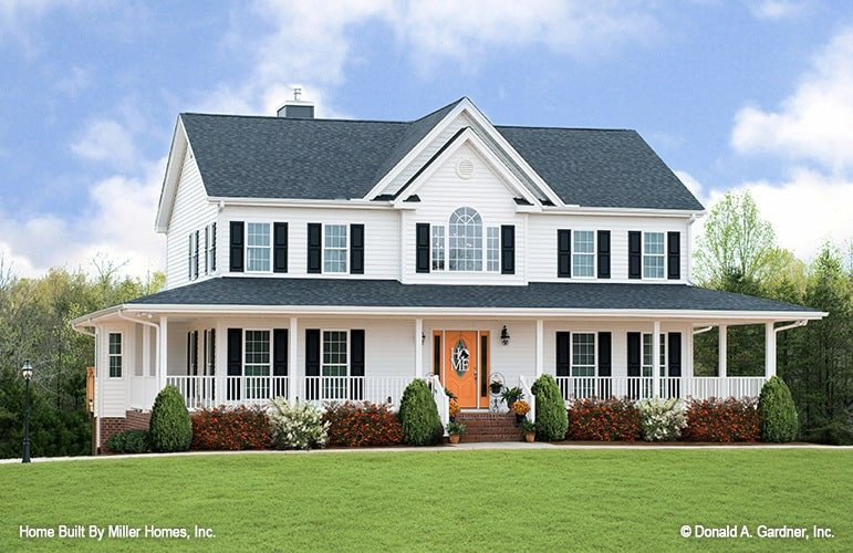 This farmhouse-style home has a wrap-around porch topped iwth a gray roof and multiple windows.