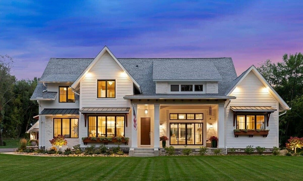 This is a modern farmhouse-style home with an abundance of glass windows and walls that give glimpses of the interiors that glow warmly. These are then complemented by the surrounding landscape.