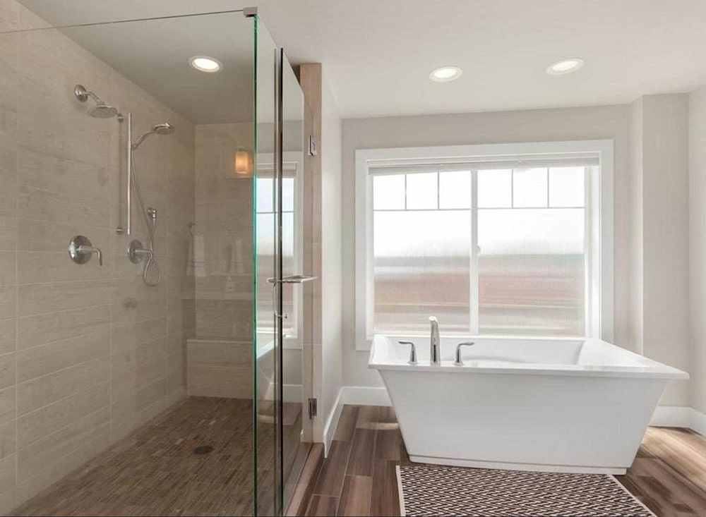 This is a bright bathroom with a white freestanding bathtub by the window beside the glass-enclosed shower area.