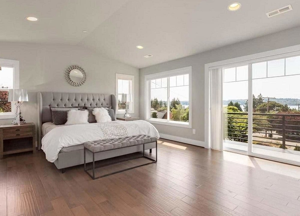 This is a spacious and bright bedroom that has a gray tufted bed that matches the light gray walls brightened by the glass windows and doors.