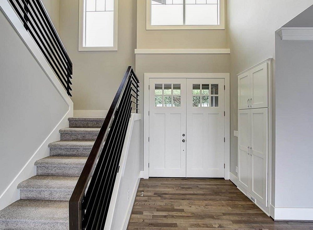 This is a simple foyer with a set of white wooden double doors, a tall ceiling and hardwood flooring that complements the light walls.