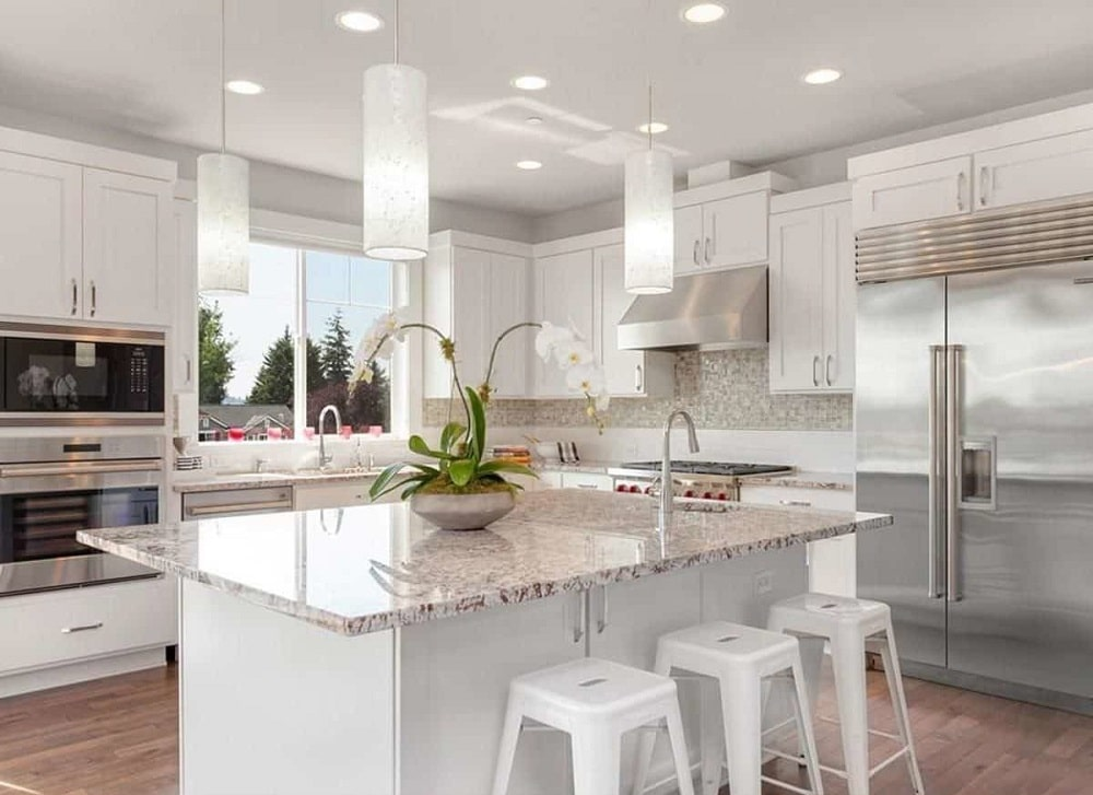 Kitchen with white cabinetry, stainless steel appliances, mosaic tile backsplash, granite countertops, and a breakfast island. These are then complemented by the natural lights coming in from the window.