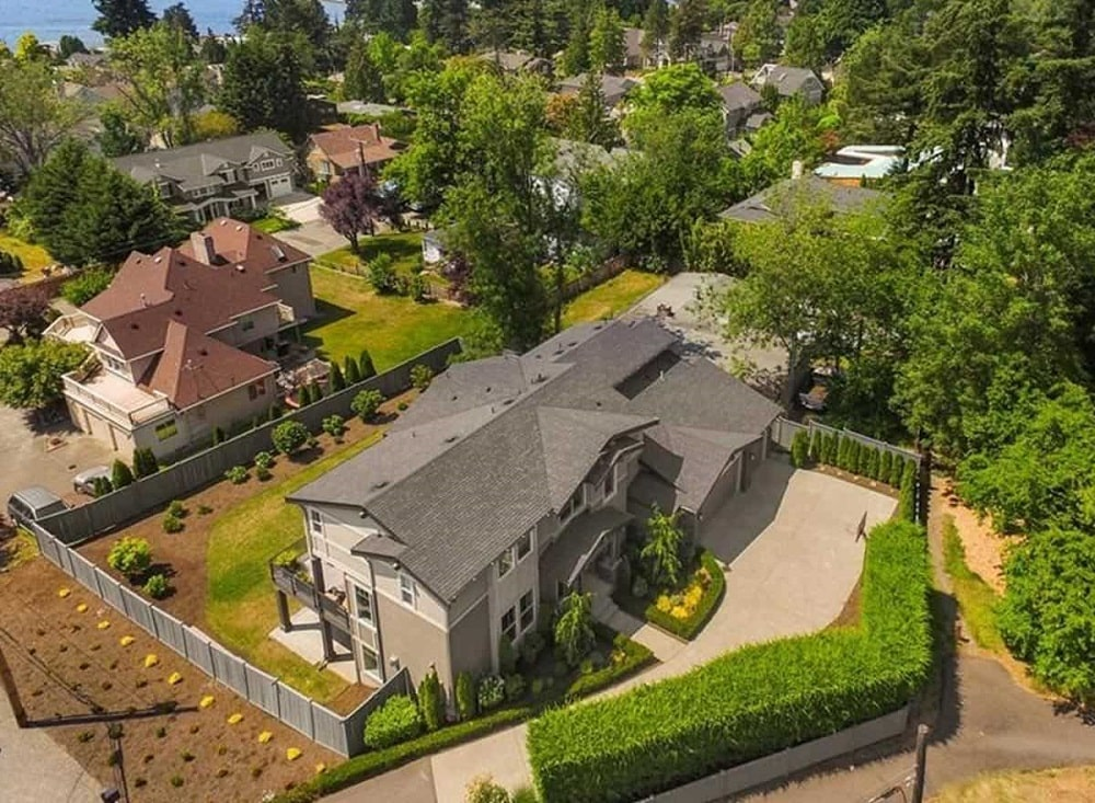 This is an aerial view of the house showcasing the surrounding landscaping that has large hedges of shrubs, miniature gardens by the entrance and a grass lawn at the back of the house.