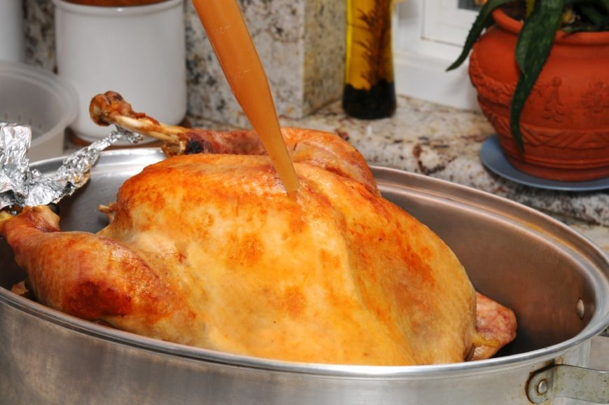 A close look at a roasted chicken being basted.