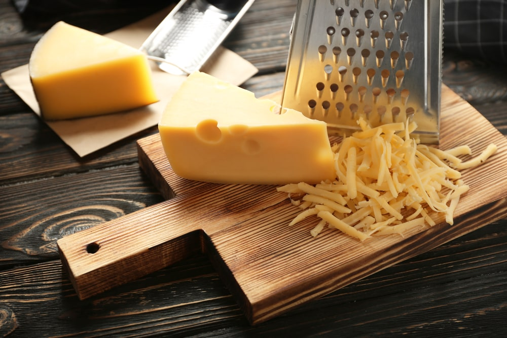 Pieces of cheese with cheese graters on chopping boards.