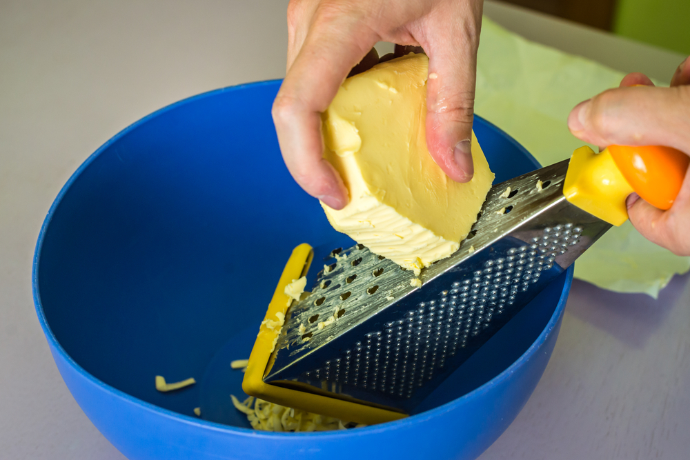 A close look at a huge chunk of butter being grated.