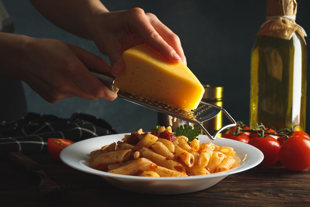 A handheld cheese grater grating cheese over pasta.