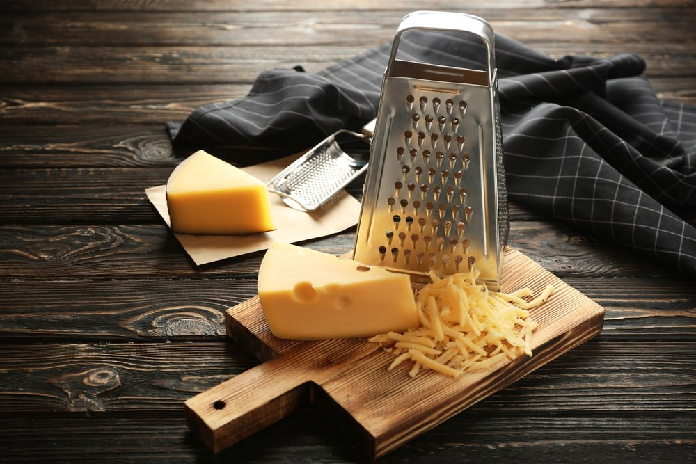 A box grater with a piece of cheese on a chopping board.