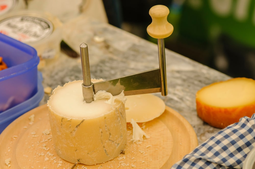 A rotary cheese grater with a wheel of cheese underneath.