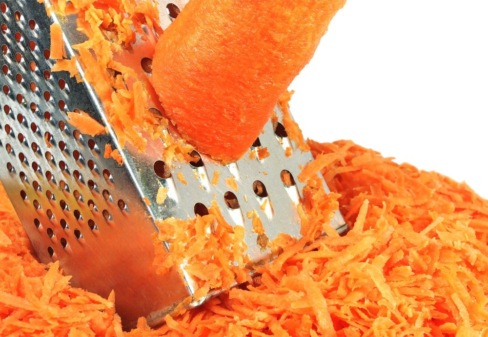 A piece of carrot grated with a vegetable grater.