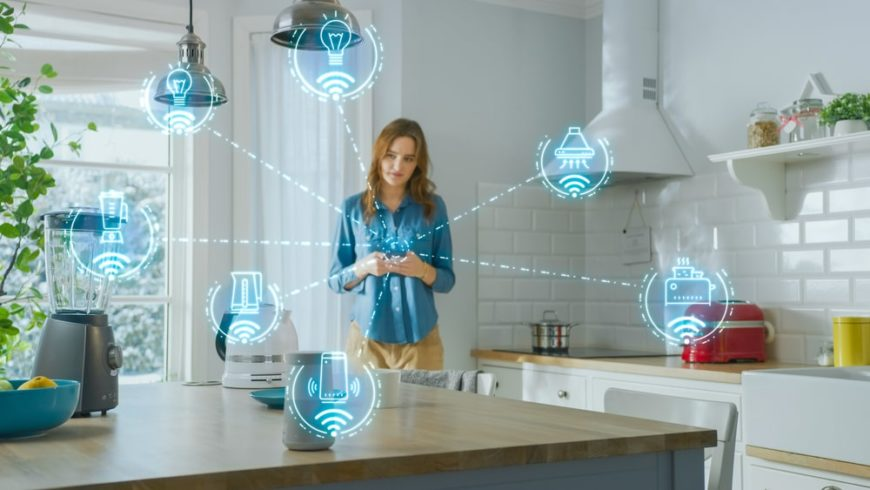 A woman in the kitchen controling the electronics with her phone.