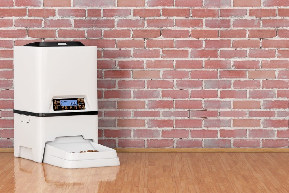 This is an automatic pet feeder placed against a red brick wall.