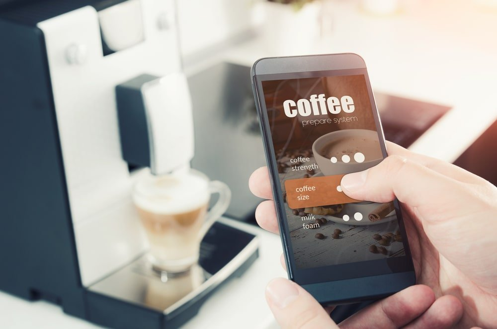 A man controlling the coffee maker with his phone.