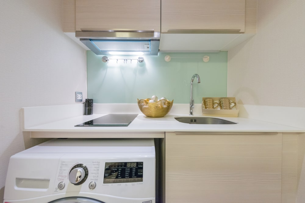 A kitchenette with an electric stove and a smart hood above it.