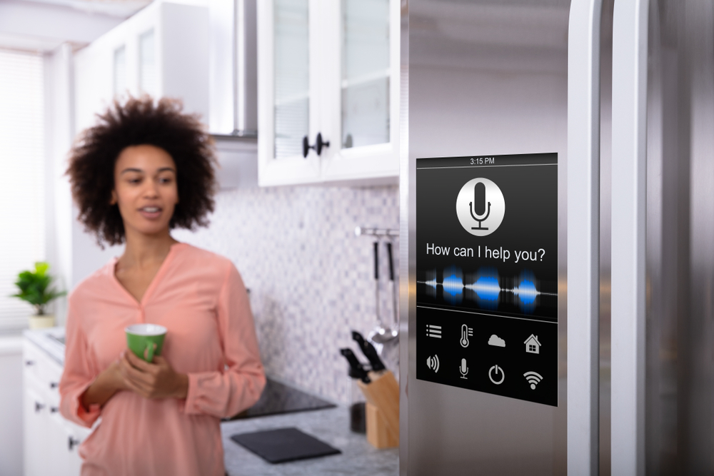 A woman with a smart fridge in the kitchen.
