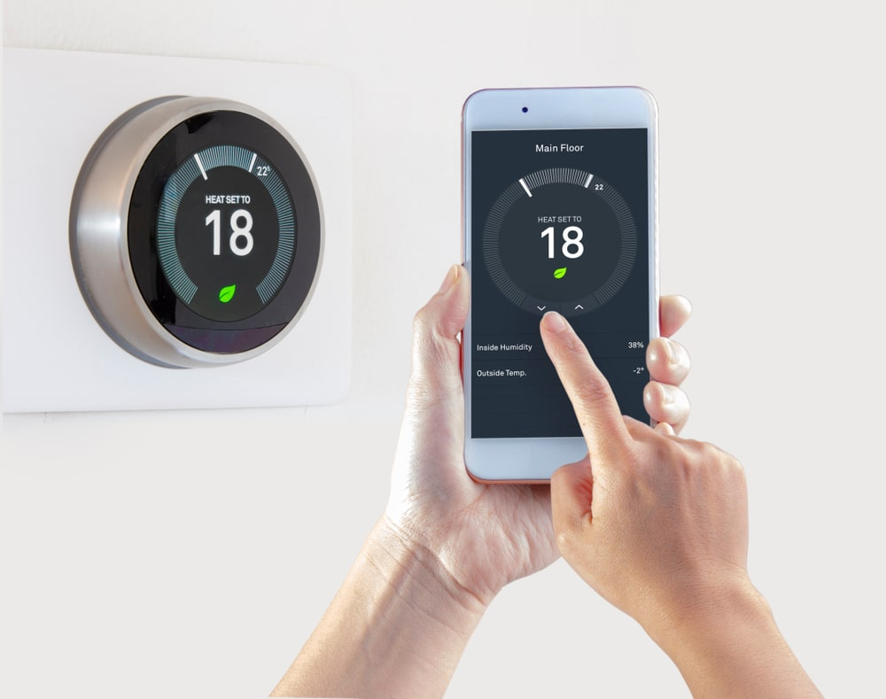 A woman controlling the thermostat with her phone.