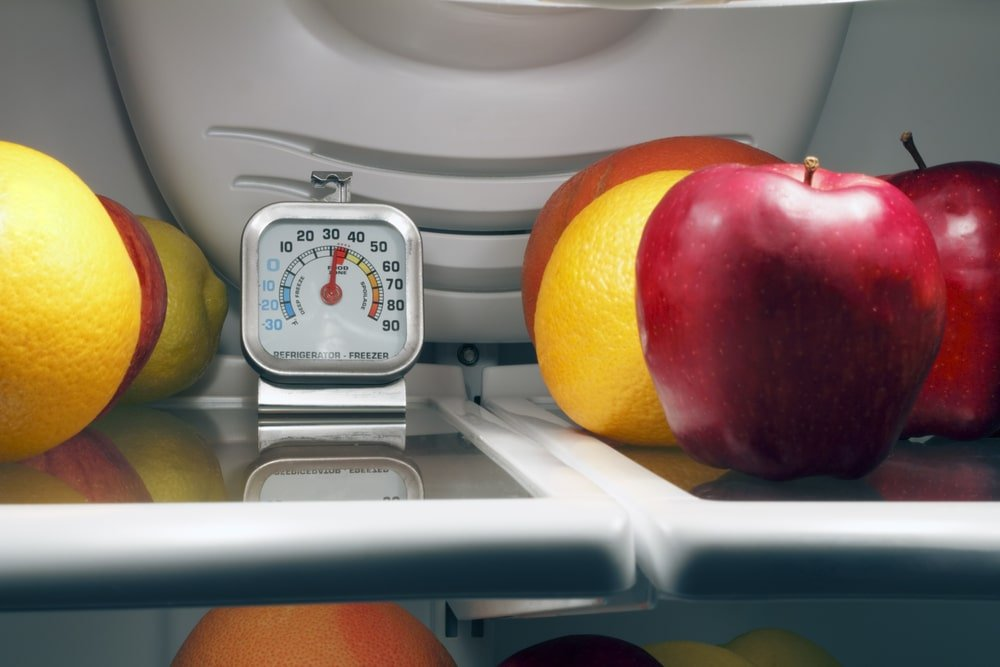 A refrigerator thermometer in the fridge with some fruits.