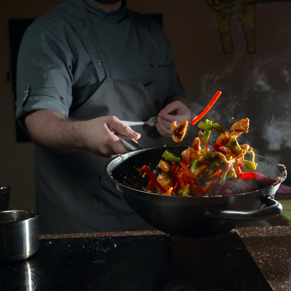 A chef cooking on a wok pan.