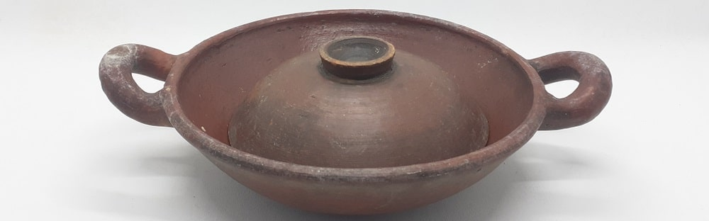 A close look at an earthenware frying pan with cover.