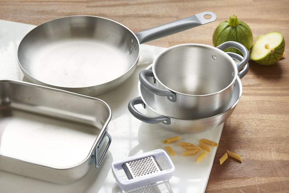 A set of aluminum cookware on a wooden table.