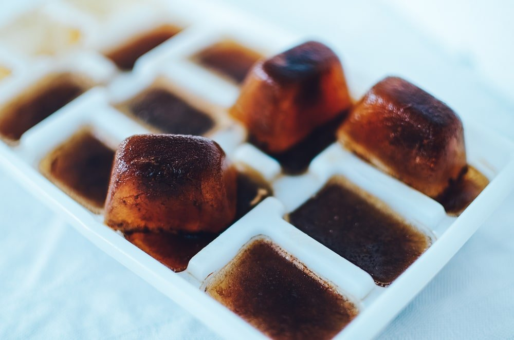 Frozen coffee ice cubes in an ice cube tray.