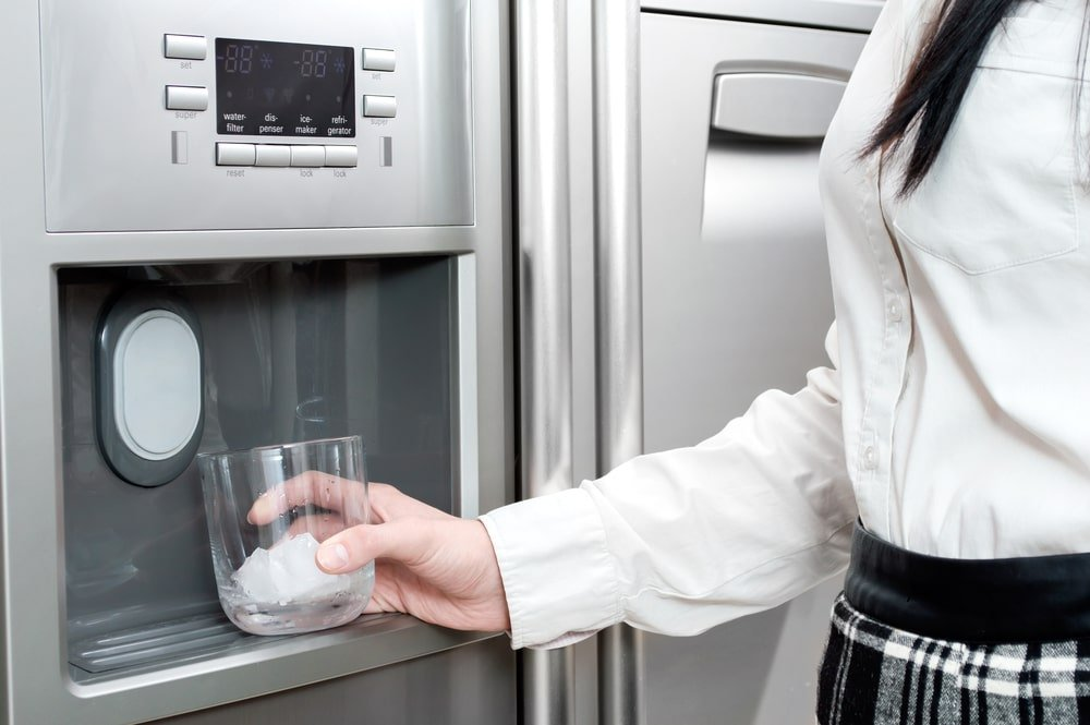 A woman getting ice from a cube ice maker.