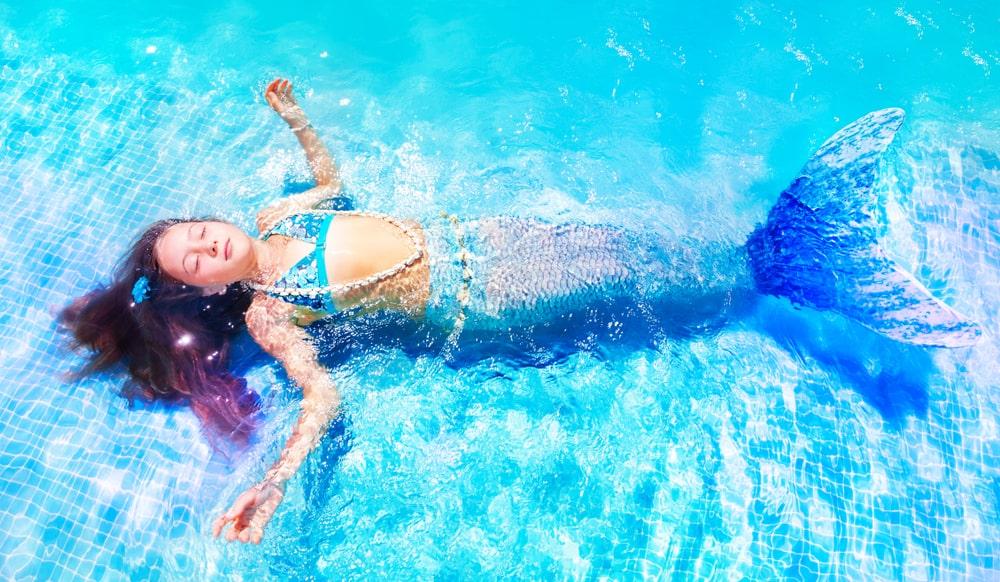 A girl in a blue mermaid costume.
