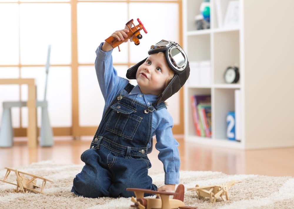 A toddler playing with toy airplanes on the floor.